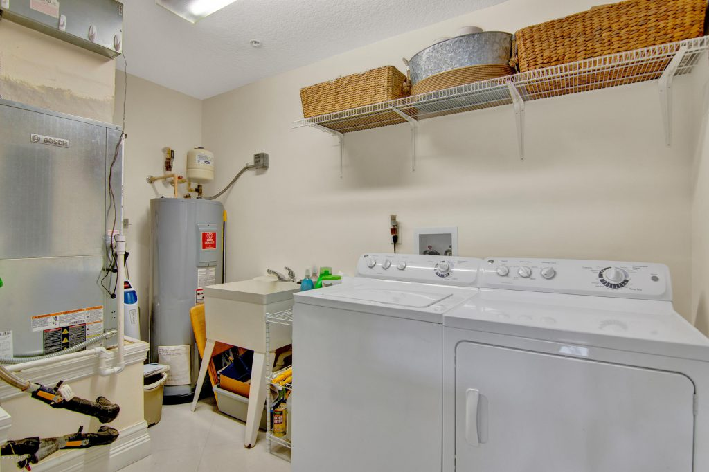 Laundry room with standard washer and dryer and standard tank water heater next to them