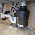 New garbage disposal installed on the right side of the sink set with new plumbing