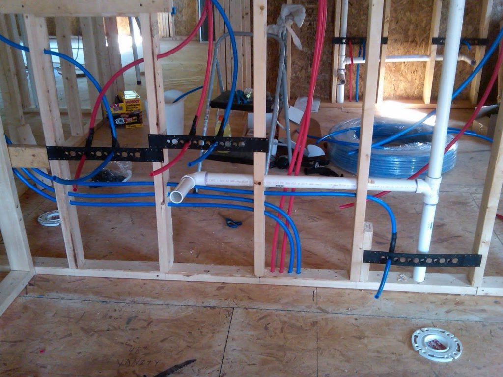 Structure being built, mostly wood, with colorful PEX piping be ran through the wood