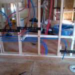 Red and blue PEX piping ran through studs and brackets for a new construction bathroom